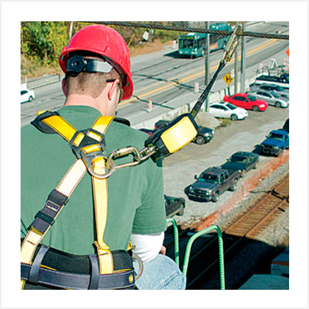 Construction worker wearing safety harness for working at heights