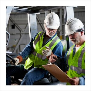 Two men in on a forklift consulting a clipboard